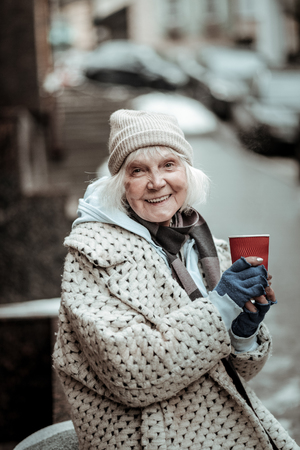 Sincere happiness. Joyful aged woman feeling absolutely happy while holding a cup with tea Imagens