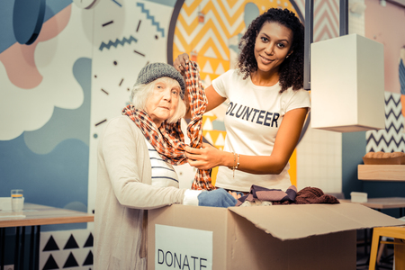 Try it on. Pleasant afro American woman smiling while helping a homeless woman to wear a scarf