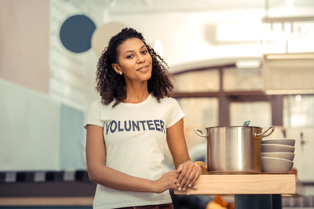 The soup is ready. Joyful afro American woman smiling while standing near the saucepan