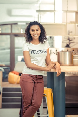 Public canteen. Positive afro American woman working in the kitchen while preparing soup