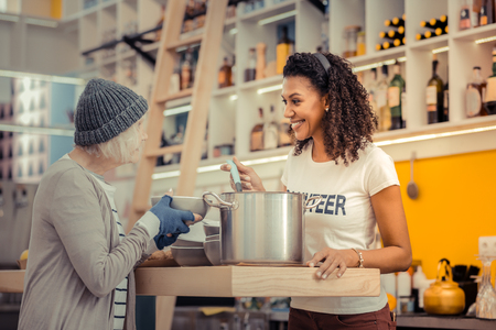 Delicious lunch. Positive nice woman holding a ladle while giving the soup to a homeless woman Stok Fotoğraf