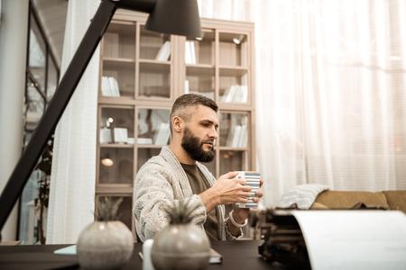 Tiempo en gabinete. Hombre serio pensativo en cardigan tejido llevando una gran taza de té mientras está sentado solo