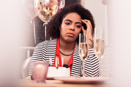 Sad holiday. Depressed afro American woman sitting at the table while being alone for holiday Archivio Fotografico