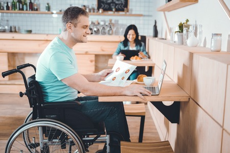 Remote job. Disabled handsome pleasant man working remotely in a cafe