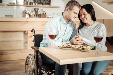 No matter what. Handsome disabled man holding womans hands having lunch