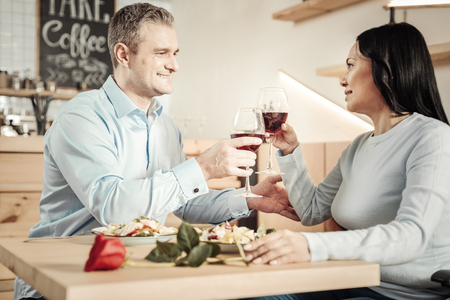 Wine time. Charming smiling man and happy nice woman holding glasses of wine having a date Banco de Imagens
