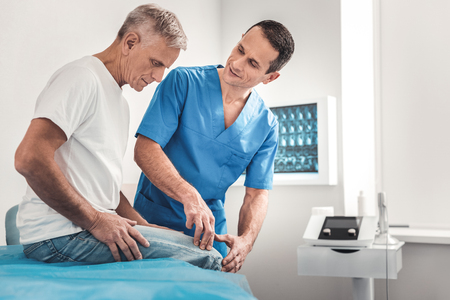 Talking to patient. Chiropractor wearing blue uniform talking to his patient while working very busy all day long