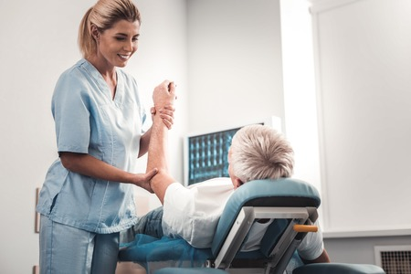Talking to patient. Smiling appealing skillful chiropractor feeling cheerful and joyful while talking to her patient Stockfoto