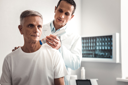 Coming to chiropractor. Man wearing plain white shirt coming to professional chiropractor for checking his shoulder Фото со стока