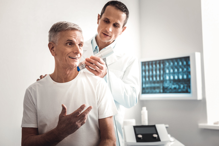 X-ray specialist. Experienced professional smart x-ray specialist feeling responsible while examining shoulder of patient Banco de Imagens