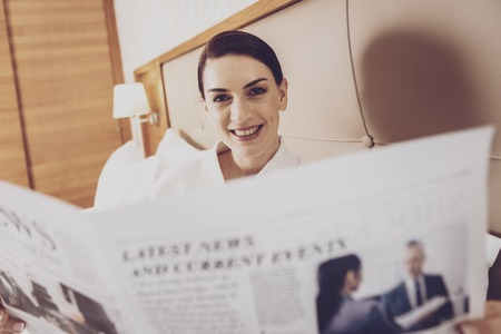 Morning newspaper. Cheerful positive woman lying on the bed with morning newspaper in hands while looking at camera with a smile on her face 스톡 콘텐츠
