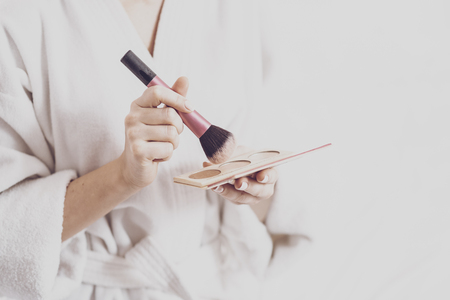 beauty. Close up of young woman in a bathrobe holding a powder brush in her hand and corrector pallet for the face