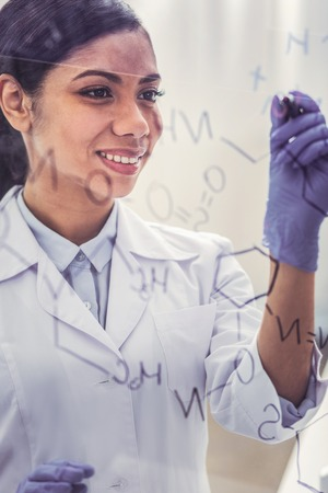 Young chemist. Young charming dark-haired chemist wearing glove feeling occupied while writing molecular chain on glass board