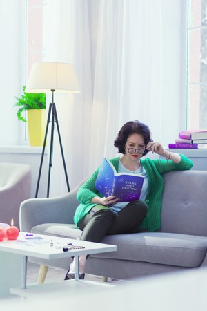 Influence of stars. Serious smart woman reading a book while enjoying astrology