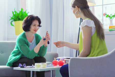 Powerful protection. Positive friendly woman holding a special amulet while giving it to her client 스톡 콘텐츠