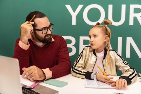 Busy day. Dark-haired bearded adult teacher wearing eyewear and his pupil feeling busy while working at the lesson Stock fotó