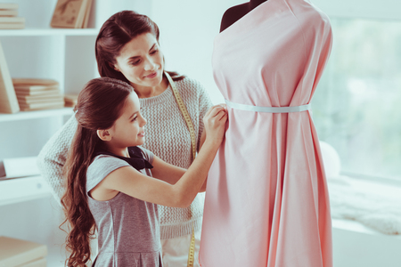 Eyecatching. Waist up of pleasant little girl putting a stripe on the mannequin while her mother standing closely with a measuring tool round her neck Stock Photo