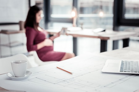 Pregnant freelancer. Beautiful pregnant freelance worker feeling relieved while having coffee break in modern office 스톡 콘텐츠