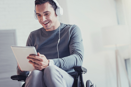 Digital technology. Nice disabled man wearing headphones while using a tablet