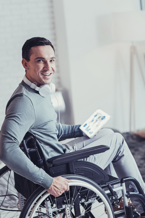 Physically disabled. Delighted handsome man sitting in the wheelchair while being paralyzed Stock Photo