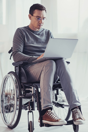 Smart freelancer. Serious handicapped man sitting in the wheelchair while focusing on his work