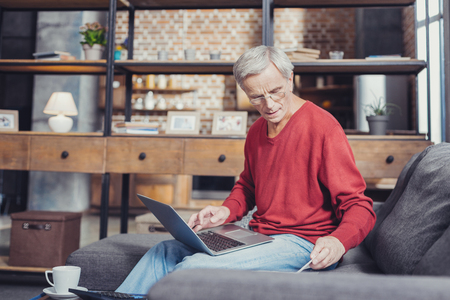 Progressive pensioner. Clever progressive aged man sitting on a sofa and holding a convenient laptop on his knees