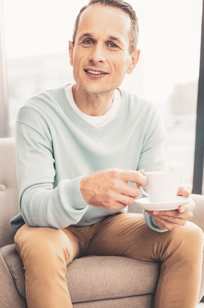 Nice tea. Handsome successful man feeling relaxed smiling while tasting nice tea sitting in the kitchen