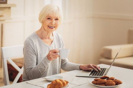 Business letter. Elderly smiling woman feeling amazing while eating tasty biscuits typing important business letter