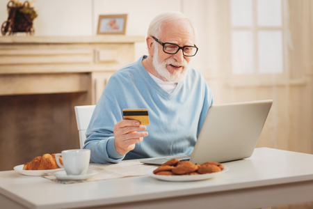 Conducting transaction. Elderly modern man feeling involved in conducting transaction while paying for monthly health insurance