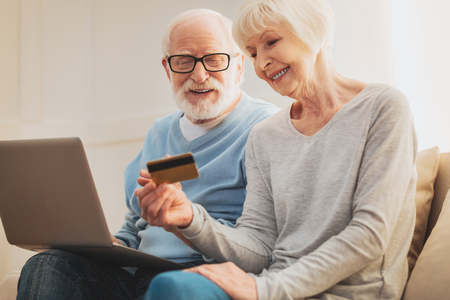 Social card. Couple of loving cute pensioners taking social card while receiving discounts for some services