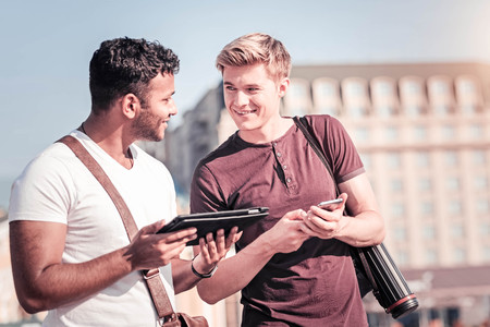 Are you sure. Attractive brunette standing in semi position and holding tablet while looking at his friend Stock Photo