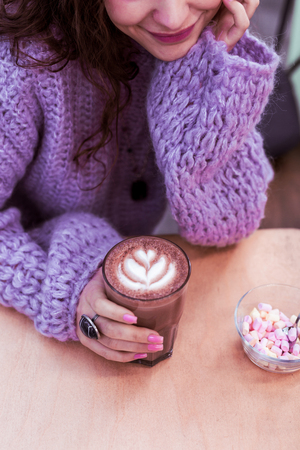 Colored marshmallow. Pretty smiling lady in oversize violet sweater and with dark bulky accessories
