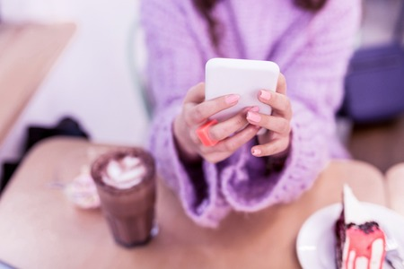 Chocolate cake nearby. Girl with accurate pink manicure typing messages on smartphone while being surrounded with goodies