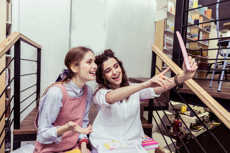 Actively gesturing. Active young dark-haired lady raising her hand with tablet and making photo with friend