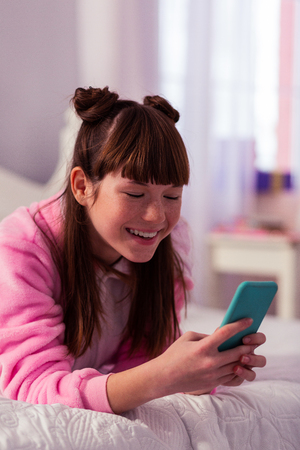 Joyful mood. Positive delighted teenager keeping smile on her face wile staring at her gadget