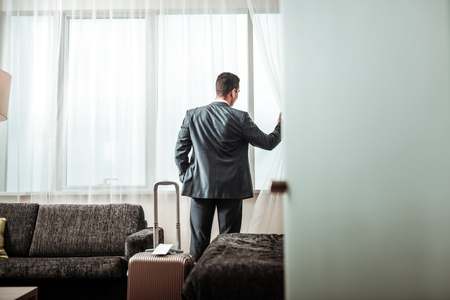 Checking city view. Dark-haired successful businessman checking the city view from his hotel room