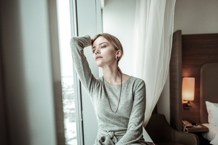 After coming home. Young appealing stylish woman feeling relieved after coming home after work