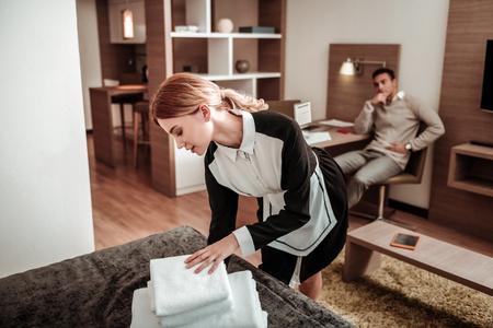 Femme de ménage de l'hôtel. Belle femme de chambre d'hôtel vêtue d'un uniforme blanc et noir apportant des serviettes blanches le matin