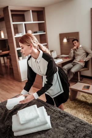 Sirvienta con cola de caballo. Criada de hotel profesional trabajadora con una bonita cola de caballo organizando toallas en la cama Foto de archivo