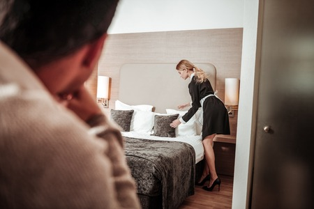 Feeling uncomfortable. Young hotel maid feeling uncomfortable while man watching her working
