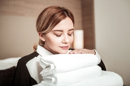 Smelling towels. Blonde-haired young housekeeper with nice natural makeup smelling towels