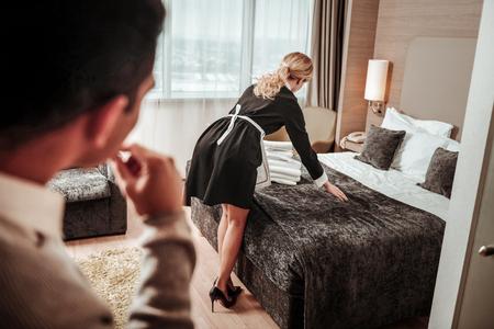 Debout avec le dos. Femme de chambre mince et blonde debout dos au client de l'hôtel Banque d'images