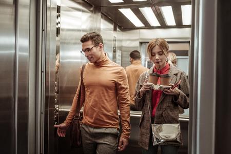 Cappuccino schlürfen. Frau nippt an ihrem Cappuccino zum Mitnehmen, während sie mit ihrem Mann mit dem Aufzug fährt