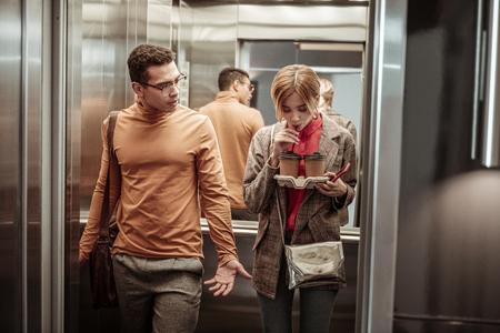 Coffee in elevator. Slim blonde-haired fashionable girlfriend drinking coffee in the elevator