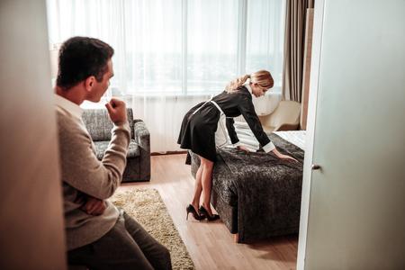 Femme de ménage aux cheveux blonds. Jeune femme de ménage aux cheveux blonds travaillant dans une chambre de luxe spacieuse