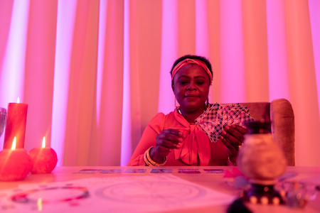Fortune-teller at work. African american plump fortune-teller wearing ethnic adornments doing Tarot reading Archivio Fotografico