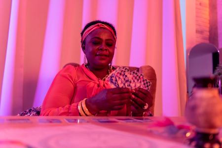 Divination. African american plump fortune-teller wearing ethnic adornments looking interested while doing reading Tarot Imagens