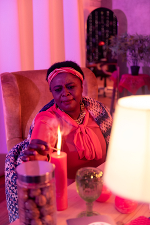 Lighting a candle. African american plump fortune-teller wearing ethnic adornments looking concentrated while holding a burning match Stock Photo