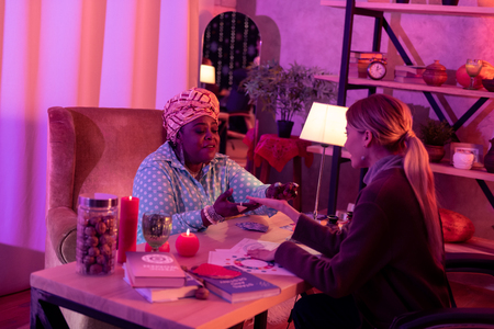 Prediction. African american plump fortune-teller wearing a huge ring telling the prediction to the client