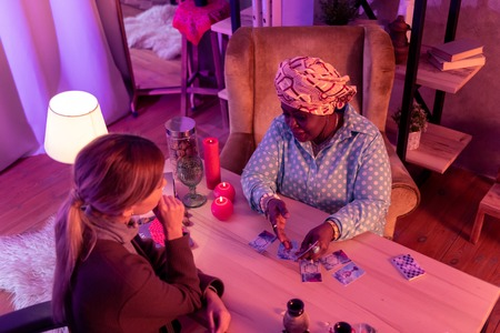 Reading details. African american plump fortune-teller wearing a huge ring explaining the details to the client 写真素材